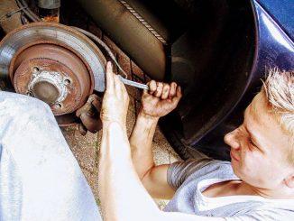 Mann beim austauschen einer Bremsscheibe