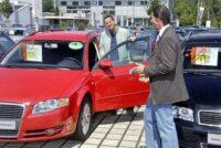Käufer informiert sich beim Gebrauchtwagen-Händler