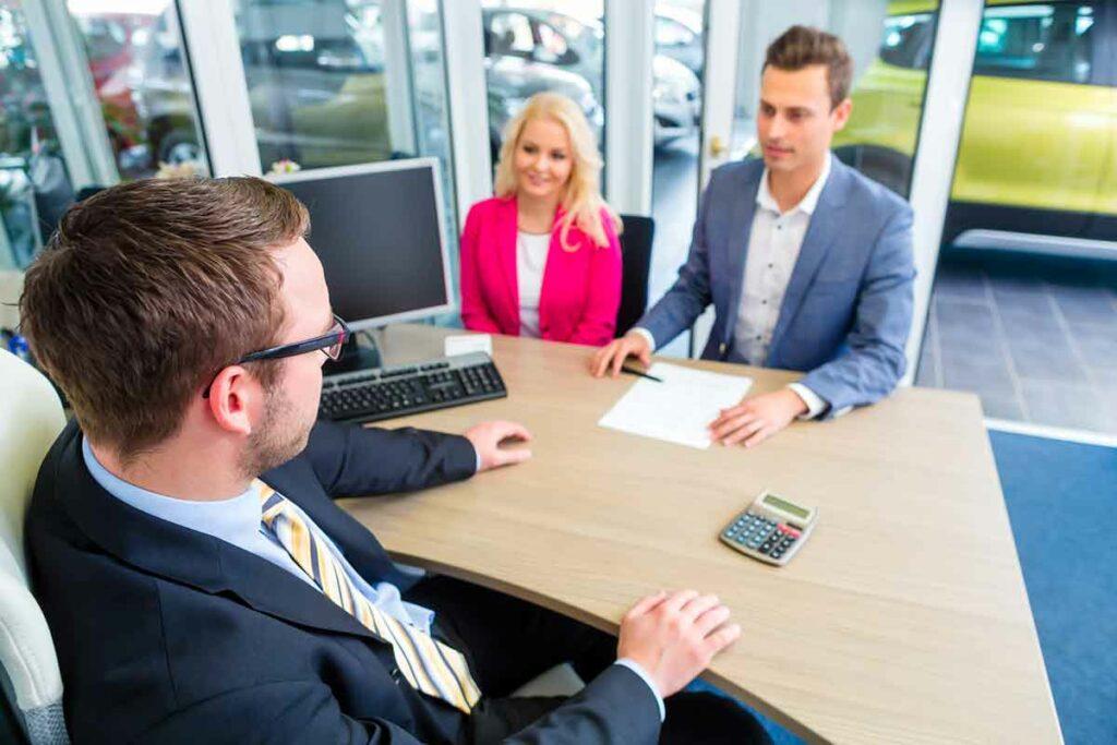 Paar in Verhandlungen bei einem Autokredit