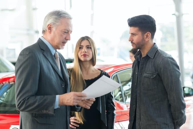 Autohändler prüft die Gebrauchtwagenfinanzierung mit den Kunden